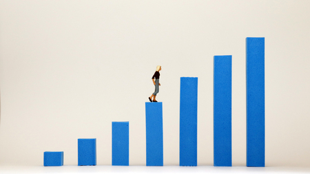 A miniature woman walking on the bar graph. The concept of constraints on womens promotion in the workplace.
