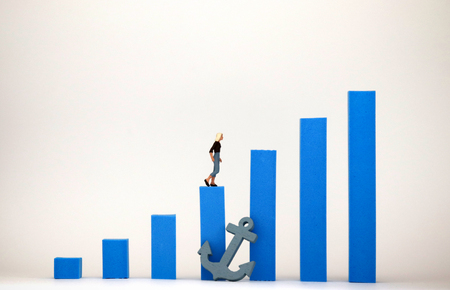 Blue bar graph and miniature woman. Social environment concept that makes it difficult for women to be promoted.