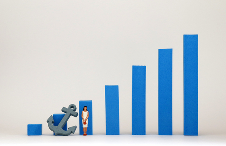 Blue bar graph and miniature woman. A social reality concept with limitations in womens promotion.