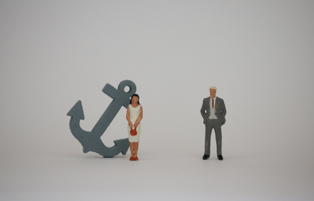 A miniature woman standing with gray anchor next to a miniature man standing. A biased treatment concept for women and men in society.