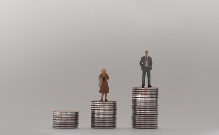 A miniature man and a miniature woman standing on a stack of coins of different heights. The concept of a gender pay gap. Stock Photo
