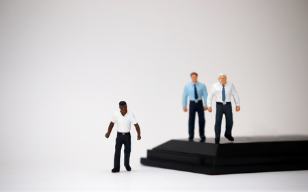 The social problem concept of racism. Miniature people of different races.