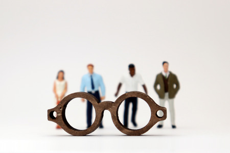 The concept of biased views is judged by appearances. Various miniature people standing behind the glasses.