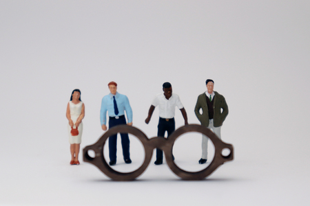 A concept of diversity and prejudice. Various miniature people standing behind the glasses.