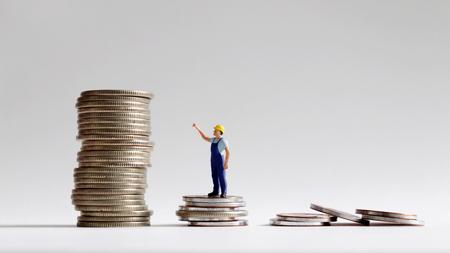 Het concept van een sociale kloof tussen arbeid en loon. De stapel munten met miniatuurmensen.