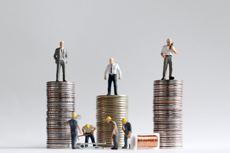 Concept of differential between the employer and the employed. The stack of coins with miniature people.