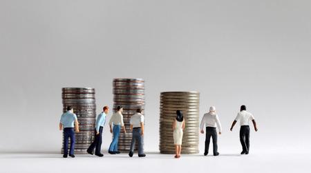 Zeitgenössisches Konzept der Wirtschaftstätigkeit. Stapel von Münzen und vielbeschäftigte Miniaturmenschen. Standard-Bild