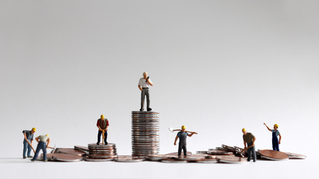 A concept of economic inequality. Pile of coins and miniature people. Archivio Fotografico