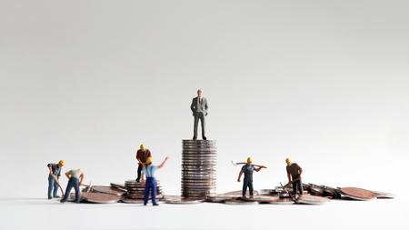 Das Konzept der Unterschiede zwischen sozialem Einkommen und Arbeit. Stapel von Münzen und Miniaturmenschen. Standard-Bild