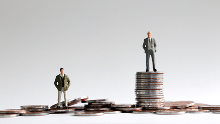 Miniature people standing on a pile of coins. Stockfoto