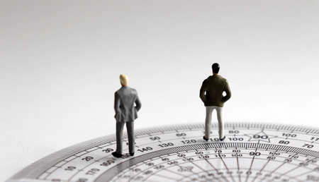 The back of two miniature men standing on protractor.