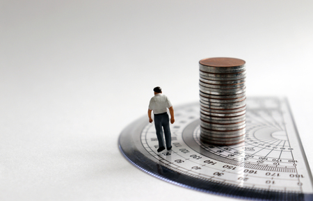 A miniature man is walking a protractor with a stack of coins.
