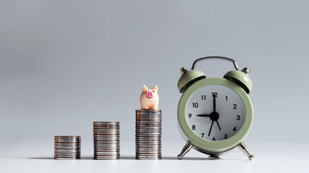 The small pink pig on a pile of coins with an alarm clock.
