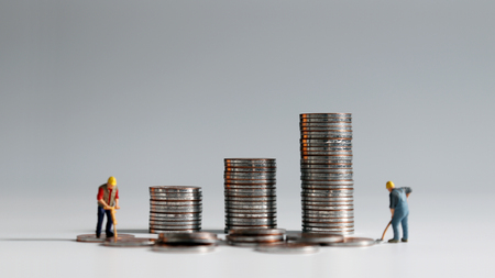 Concept of rising labor costs. A stack of coins and two miniature people.