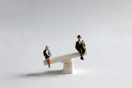 A miniature man and woman sitting on a mini seesaw.