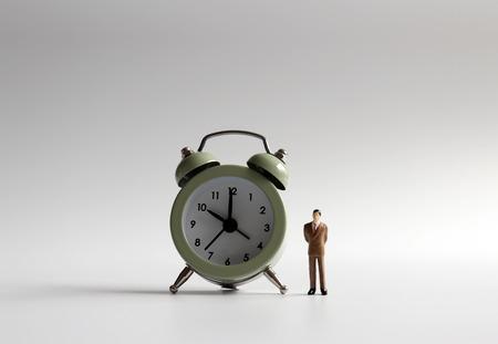 A miniature man standing next to the alarm clock.
