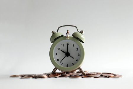 A miniature woman holding an alarm clock with coins. Stockfoto - 104348238