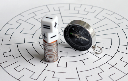 A compass is next to the arithmetic operation symbol on the stack of coin against the maze.