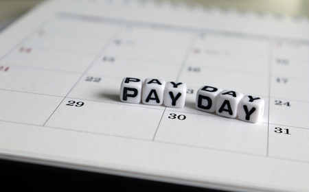 A white cube arranged in the word PAY DAY on the calendar. Фото со стока
