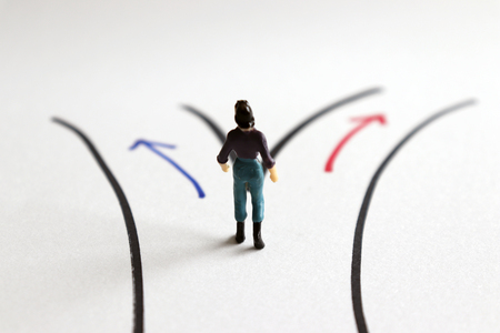 A miniature woman standing in front of two different paths.