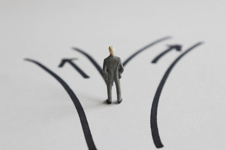 Un homme miniature debout devant deux chemins.