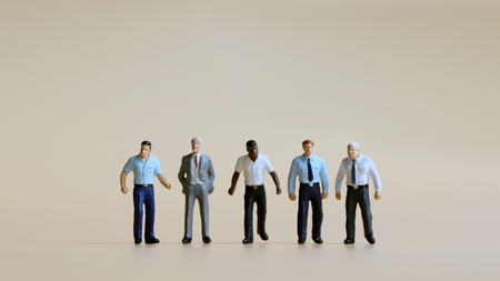 Various miniature people standing side by side. Stock Photo