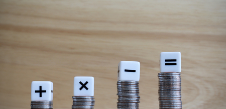 Cztery kostki symboli arytmetycznych na czterech monetach.