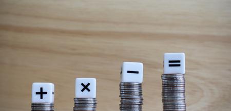 Los cuatro cubos de símbolos aritméticos encima de las cuatro monedas.