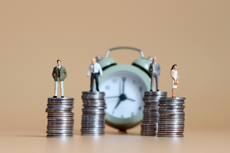 The miniature people standing on piles of coins and an alarm clock.