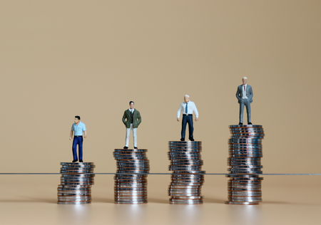 Miniature people standing on piles of coins. Concepts on the difference between promotion and benefits. Фото со стока