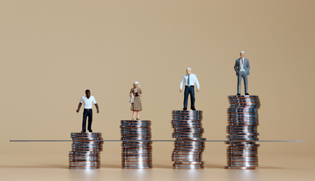 Miniature people standing on piles of coins.