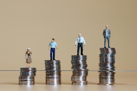 Hombres y mujeres en miniatura de pie sobre los montones de monedas. Foto de archivo