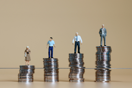 Miniature men and miniature woman standing on top of the piles of coins.