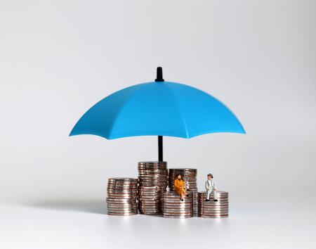 Las parejas de ancianos tienen miniaturas sentadas sobre un montón de monedas y paraguas. Foto de archivo