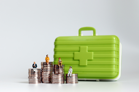 Old age miniatures sitting on a pile of coins with a medical kit. Stock Photo
