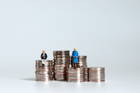 Two elderly miniature people on a pile of coins at different heights.