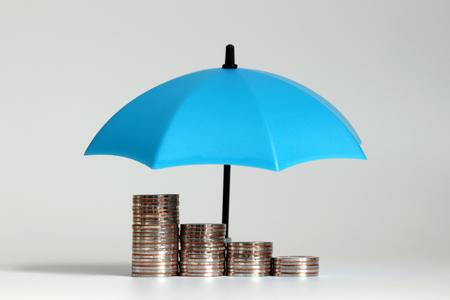 Een stapel munten en open blauwe paraplu's.