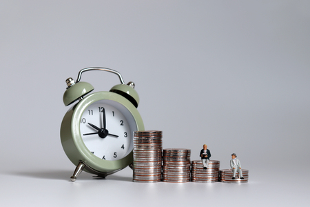 An alarm clock with an old age miniature men sitting in a pile of coins. Stockfoto