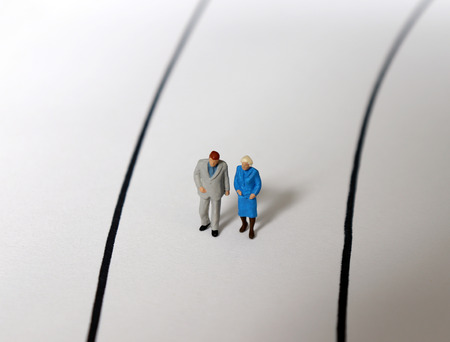 The elderly couple is a miniature walking side by side on the street.