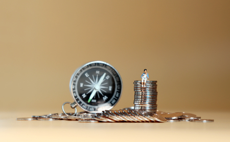 A miniature woman sitting with a baby on a pile of coins in front of a compass.