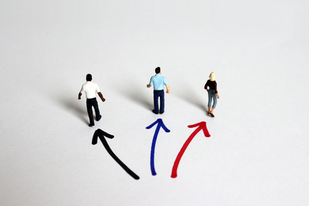 The back of three miniature people standing in three directions. Stock Photo