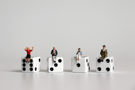 A concept of gender role conflict. Miniature men and miniature women sitting on dice.