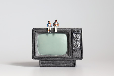 Miniature couple with baby sitting on miniature television.
