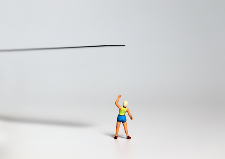 A miniature woman pointing at the edge of a cliff. 写真素材