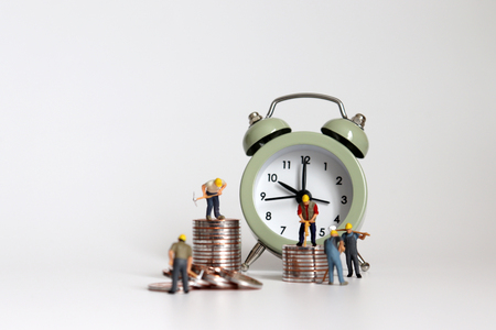 Miniature worker with alarm clocks and piles of coins.