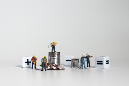 Miniature worker people with a cube with an arithmetic symbol and piles of coins. Imagens