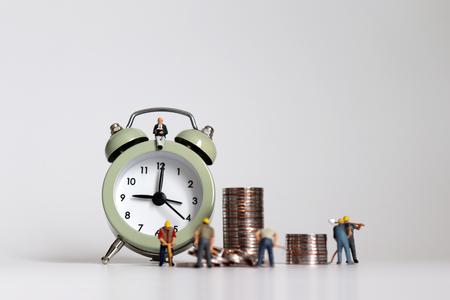 Ouvrier miniature avec des tas de pièces de monnaie. Le concept des heures de travail et des calculs de salaire.