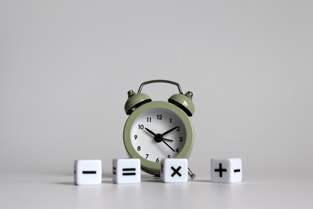 White arithmetic symbols cube and an alarm clock. 写真素材