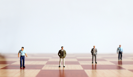 Four miniature men standing on the chessboard.
