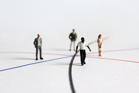 Miniature diverse people standing on different line. 免版税图像